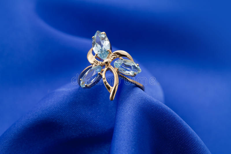 Jewelry ring with sapphire. Elegant jewelry ring with jewel stone - sapphire on a background of blue silk stock photo