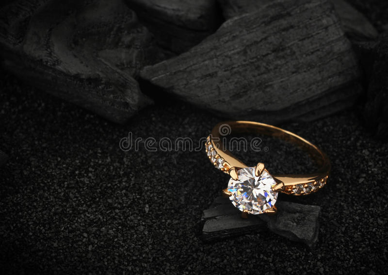 jewelry ring witht big diamond on dark coal and black sand background, soft focus royalty free stock photography
