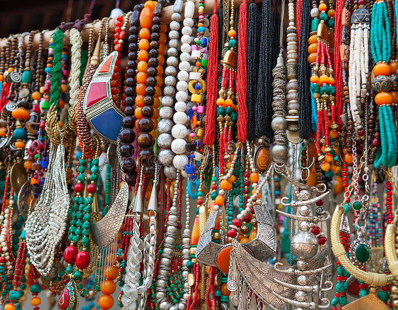 Jewelry in row of necklaces and bracelets. On summer market outdoors stock image