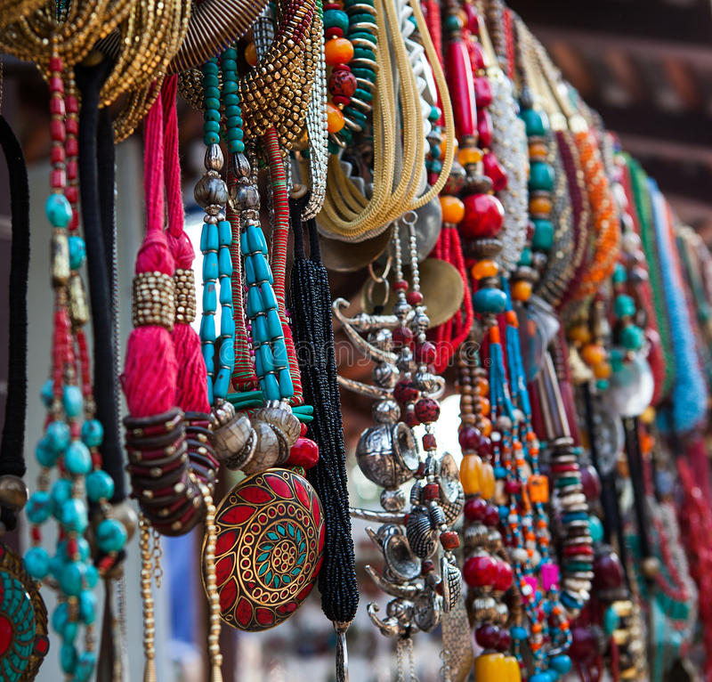Jewelry in row of necklaces and bracelets. On summer market outdoors stock photos