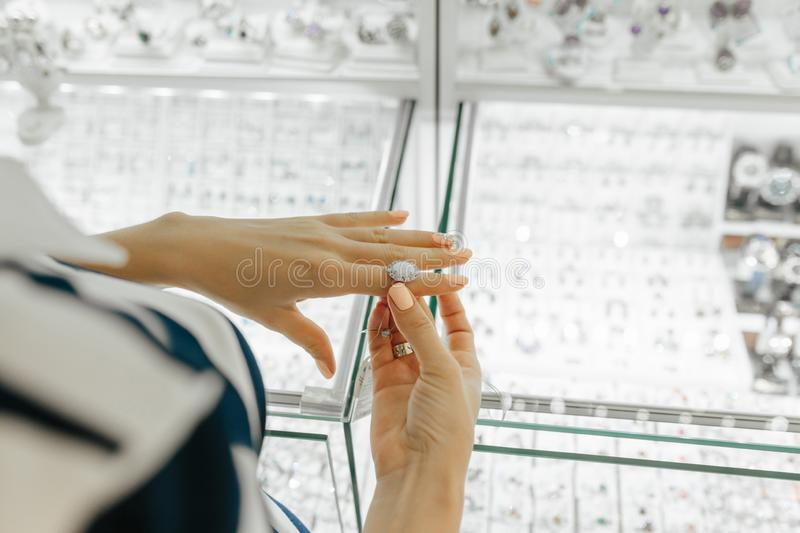 Jewelry store shop indoors - small business. Gold and diamonds for sale. Womens hands royalty free stock photo