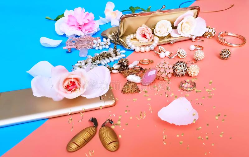 Jewelry white pearl gold rings and earrings with golden  decoration  phone and cosmetic case on modern pink and blue background wo. Men accessories stock image