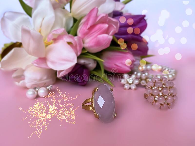 Jewelry white pearl  and pink opal gold ring on white pink coral floral background,   spring flowers for Valentine day women day royalty free stock image