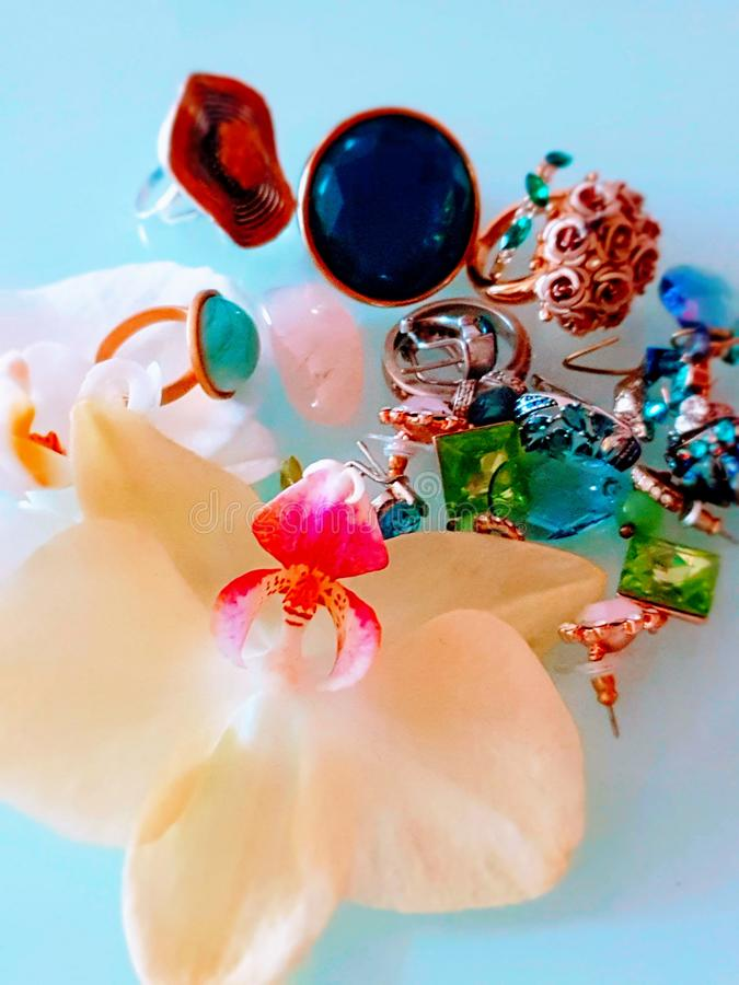 Jewelry   white pearl  rings earrings bracelet with Luxury Glamour fashion  costume  gold jewelry  red roses ,orchids on blue and. Beautiful  Jewelry   white royalty free stock photo