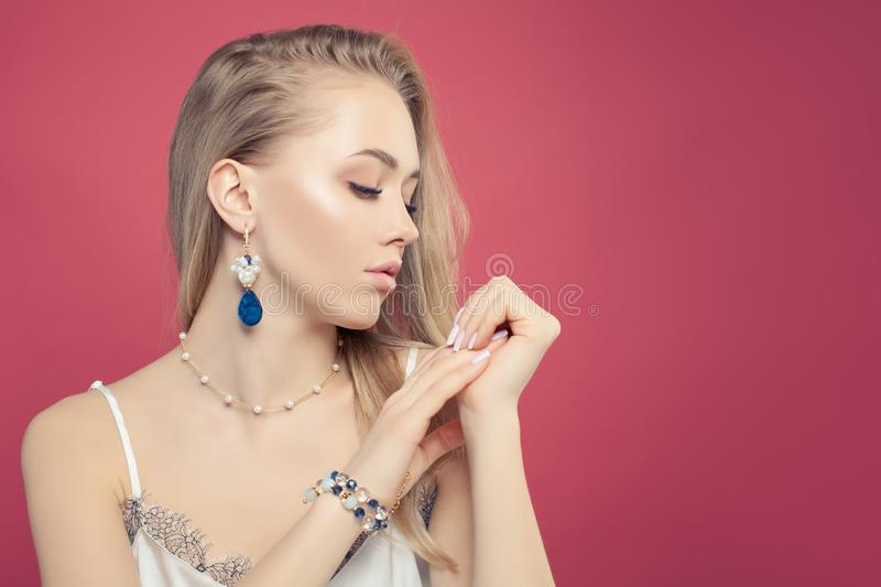 Jewelry woman portrait. Pretty girl with fashion gold jewelry with pearls on pink background stock photo