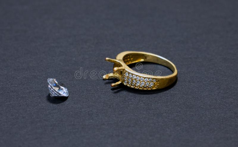 Jewelry work, gold ring with a diamond, preparation for installing a stone on a ring, dark background stock image