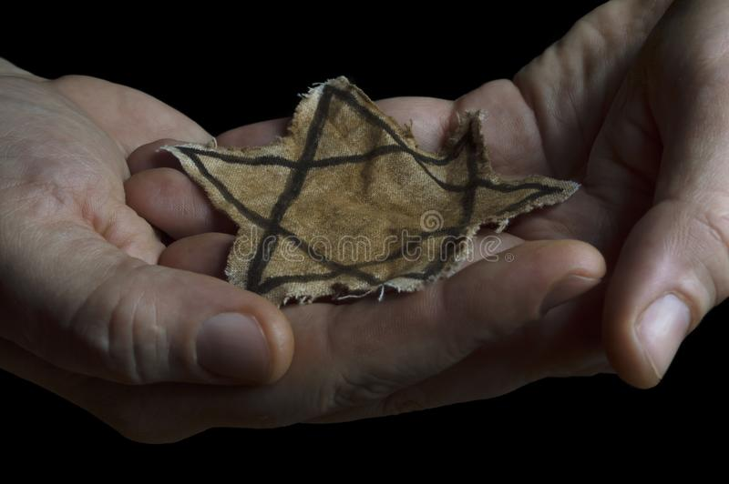 Jewish badge in the hands of a man stock photography