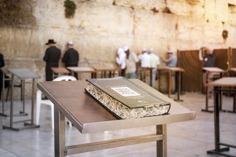 Jewish bible - Torrah on table on blurred background of praying Jews and wailing western wall. Israel. Jerusalem. JERUSALEM, ISRAEL. 24 October 2018 royalty free stock photos