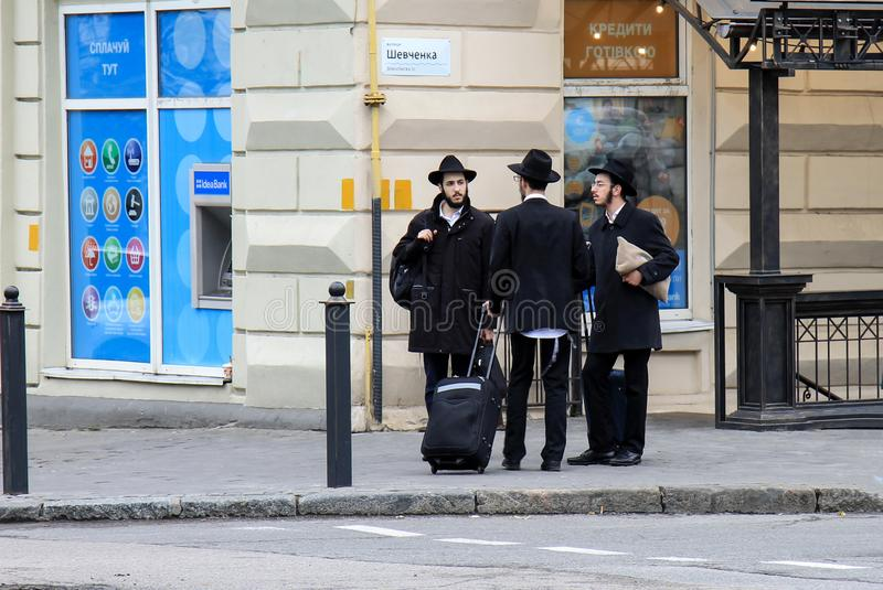 3 Jewish boys, Hasidic Jews, in black clothes and hats with suitcases and luggage stand on the street. Religious Orthodox Jew. Hasidim, Dnepropetrovsk city royalty free stock photos