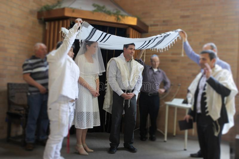 Jewish bride and a bridegroom wedding Ceremony. Jewish bride and a bridegroom married in a modern Orthodox Jewish wedding ceremony in a synagog stock photo