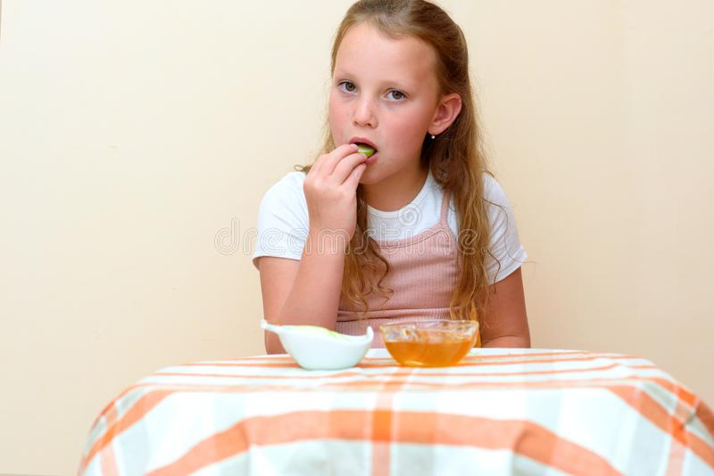 Jewish child dipping apple slices into honey on Rosh HaShanah. stock photo