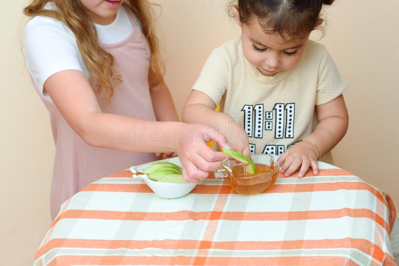 Jewish children dipping apple slices into honey on Rosh HaShanah. stock images