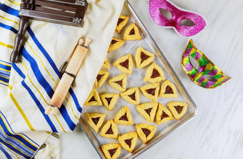 Jewish cookies Haman ears in baking pan for Purim with mask, tallit and noisemaker stock photo
