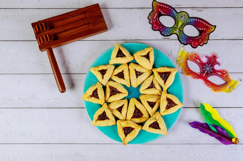 Jewish cookies Haman ears for Purim with mask and noisemaker royalty free stock photos