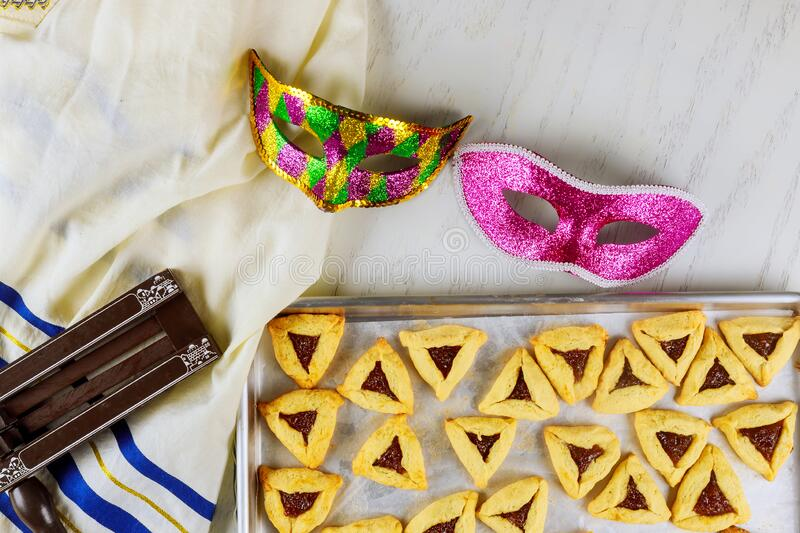 Jewish cookies Haman ears for Purim with mask, tallit and noisemaker royalty free stock photos