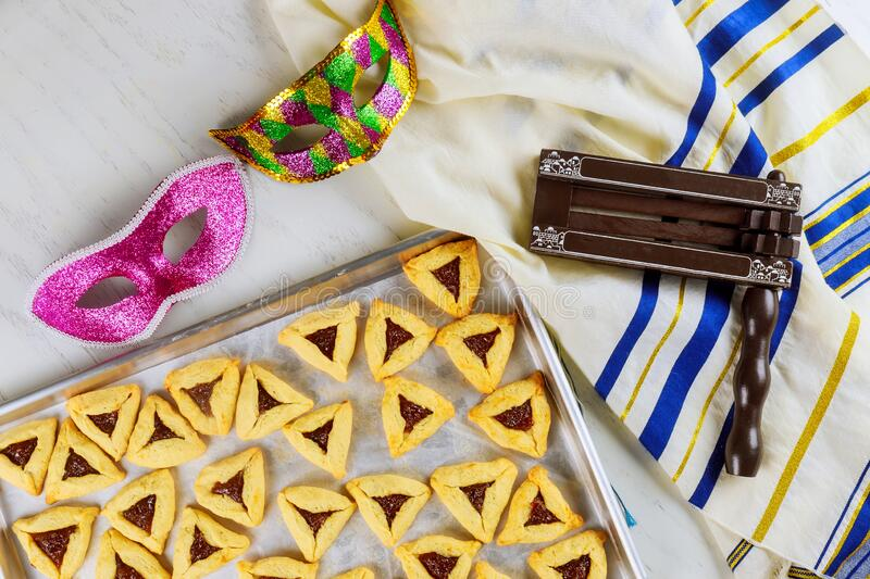Jewish cookies for Purim with mask, tallit and noisemaker stock photo
