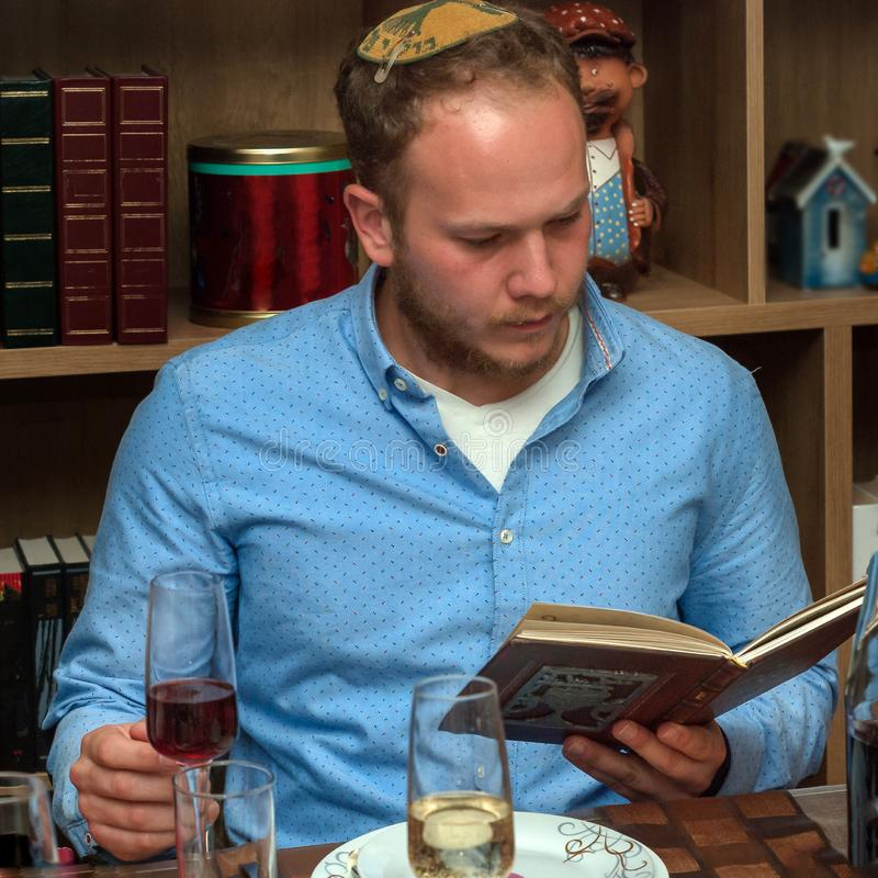 Jewish man reads from the Haggadah as they celebrate Passover. Jewish Family Celebrating Passover.Jewish man reads from the Haggadah as they celebrate Seder stock photo
