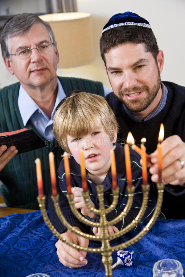 Jewish family lighting Chanukah menorah stock photos
