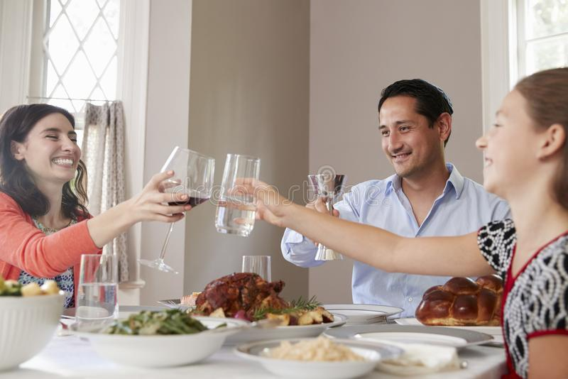 Jewish family raising glasses at the table for Shabbat meal stock photos