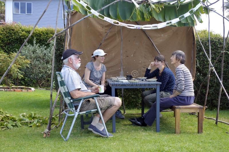 Jewish Family Sitting in a Sukkah on Sukkoth Feast of Tabernacle stock photography