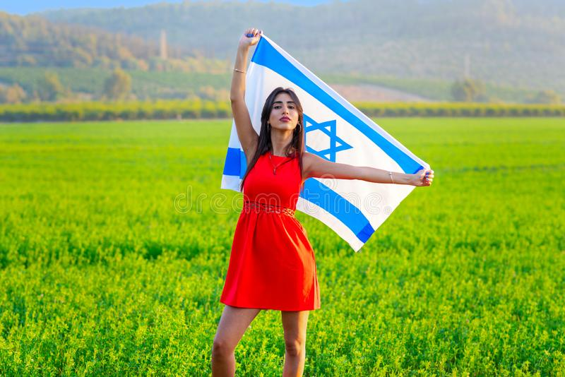 Jewish girl with flag of Israel on amazing landscape in beautiful summer. stock photography