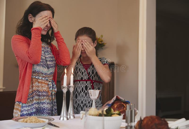Jewish girl and mother cover eyes to recite Shabbat blessing stock photography