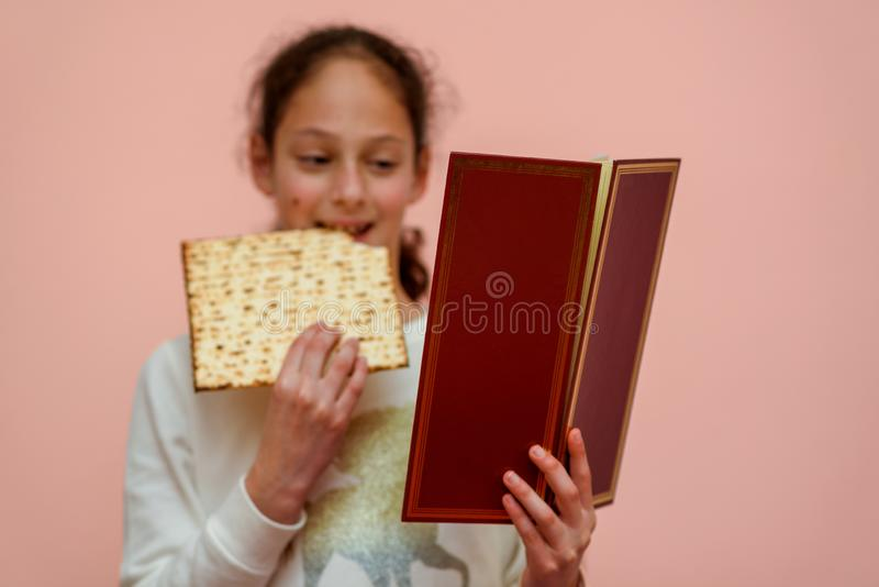 Jewish Girl Reads the Passover Haggadah and Eating Matzah. Portrait of the cute teenager girl holding matzah and reads the Passover Haggadah. Jewish child stock image