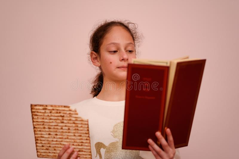 Jewish Girl Reads the Passover Haggadah and Eating Matzah. Portrait of the cute teenager girl holding matzah and reads the Passover Haggadah. Jewish child stock photography
