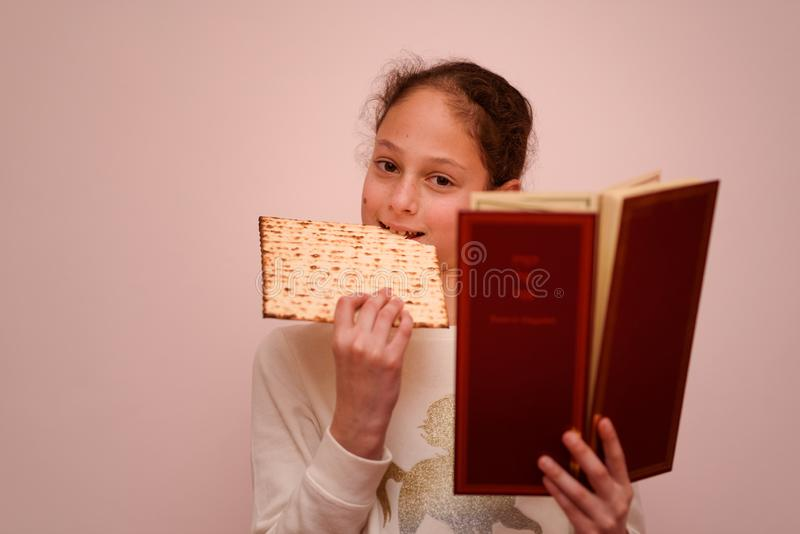 Jewish Girl Reads the Passover Haggadah and Eating Matzah. Portrait of the cute teenager girl holding matzah and reads the Passover Haggadah. Jewish child stock photo