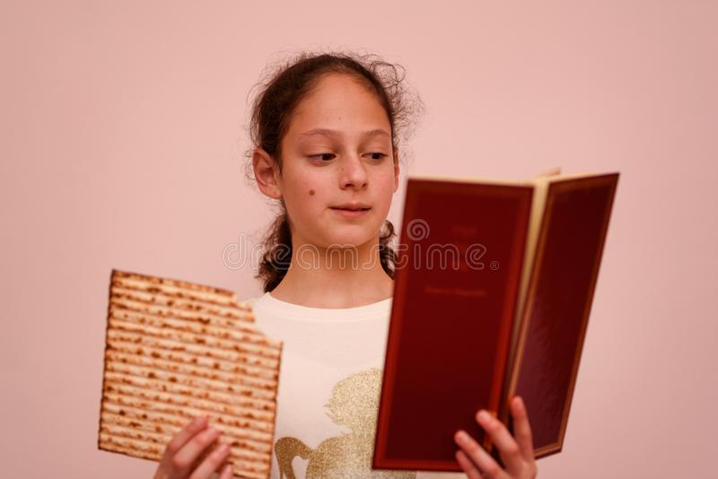 Jewish Girl Reads the Passover Haggadah and Eating Matzah. Portrait of the cute teenager girl holding matzah and reads the Passover Haggadah. Jewish child royalty free stock photography