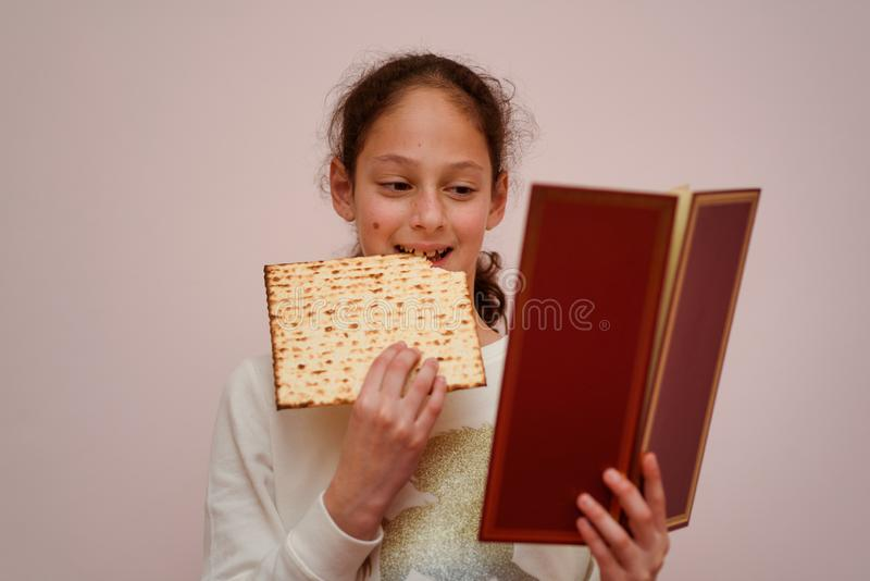 Jewish Girl Reads the Passover Haggadah and Eating Matzah. Portrait of the cute teenager girl holding matzah and reads the Passover Haggadah. Jewish child stock images