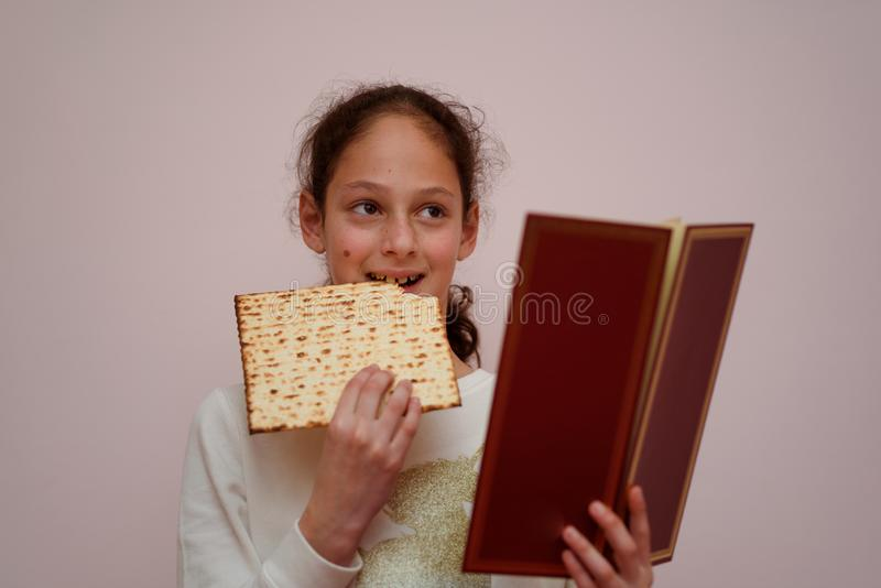 Jewish Girl Reads the Passover Haggadah and Eating Matzah. Portrait of the cute teenager girl holding matzah and reads the Passover Haggadah. Jewish child royalty free stock image