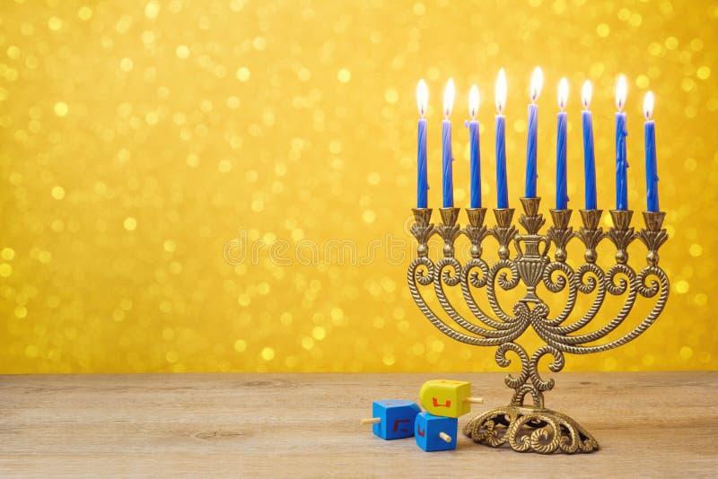 Jewish Hanukkah background with vintage menorah and spinning top dreidel over lights bokeh stock images