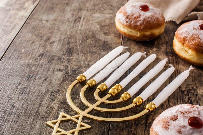 Jewish Hanukkah menorah and sufganiyot donuts on wooden table stock photography