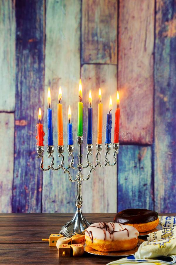 Jewish holiday hannukah symbols - menorah, doughnuts, chockolate coins and wooden dreidels. royalty free stock image