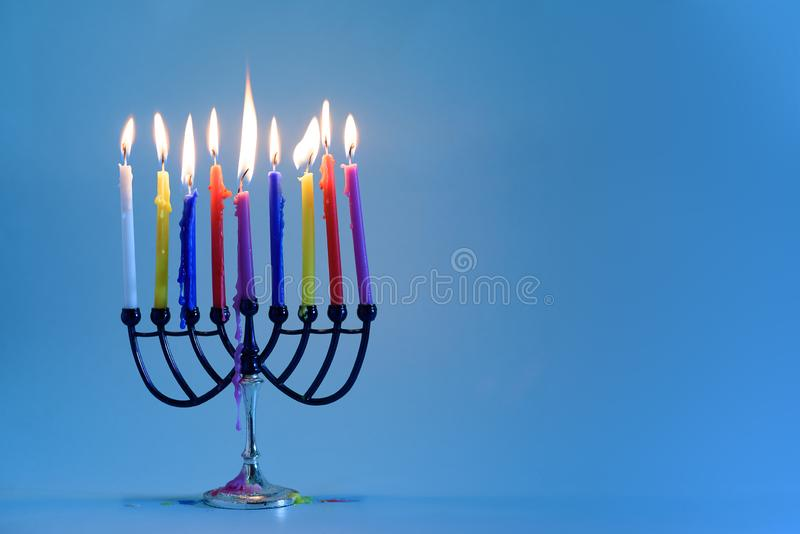 Jewish holiday Hanukkah background with menorah traditional candelabra and burning colorful candles. royalty free stock images