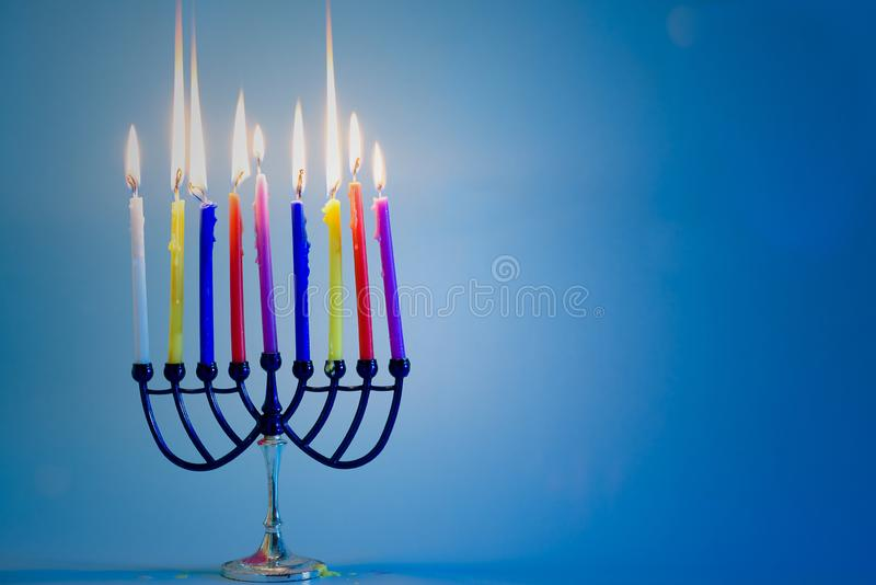 Jewish holiday Hanukkah background with menorah traditional candelabra and burning colorful candles. stock images