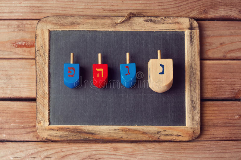 Jewish Holiday Hanukkah background with wooden dreidel spinning top and chalkboard. Jewish Hanukkah background with wooden dreidel spinning top and chalkboard stock photos