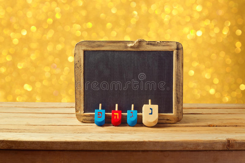 Jewish Holiday Hanukkah background with wooden dreidel spinning top and chalkboard over golden bokeh lights royalty free stock images