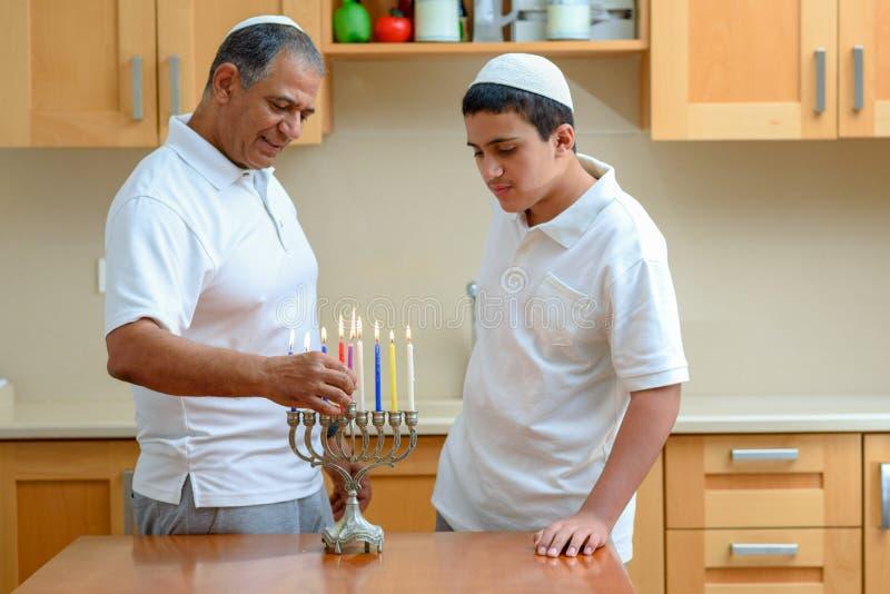 Jewish holiday Hanukkah. Jewish Dad and teenager son lighting Chanukkah Candles in a menorah for the holdiay stock photos