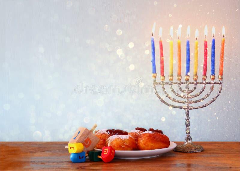 Jewish holiday Hanukkah with menorah, doughnuts over wooden table. retro filtered image royalty free stock image