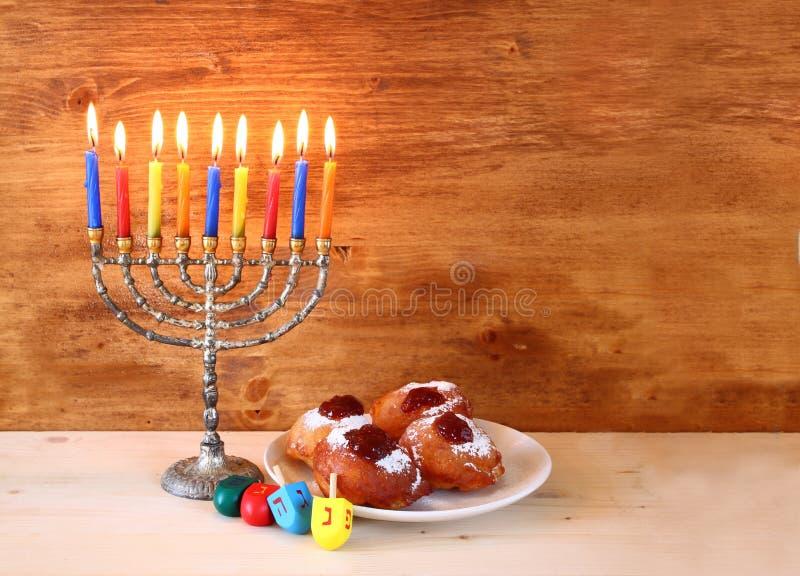 Jewish holiday Hanukkah with menorah, doughnuts over wooden table. retro filtered image. royalty free stock photos