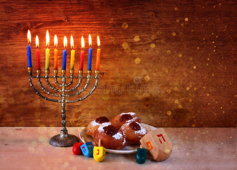 Jewish holiday Hanukkah with menorah, doughnuts over wooden table. retro filtered image royalty free stock photo