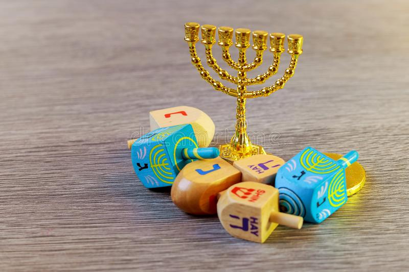 jewish holiday Hanukkah with wooden dreidels colection spinning top and chocolate coins on the table royalty free stock images