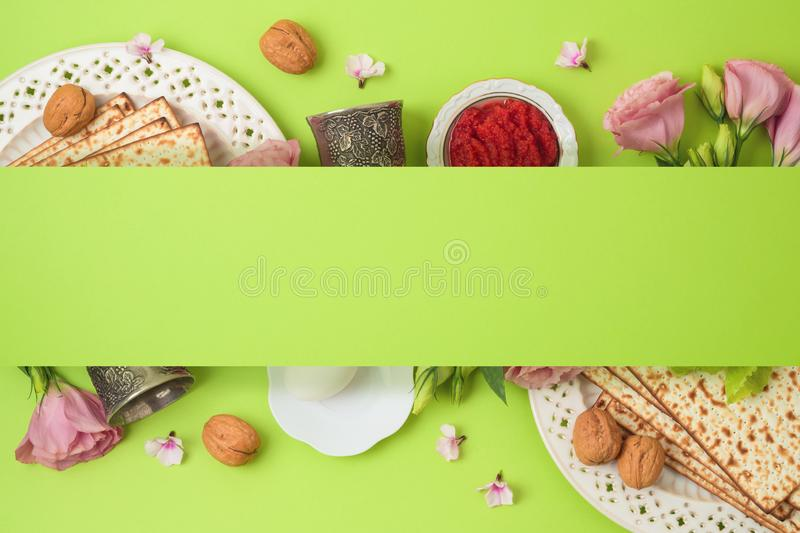 Jewish holiday Passover background with matzo, seder plate and spring flowers. Top view from above. Flat lay stock photos