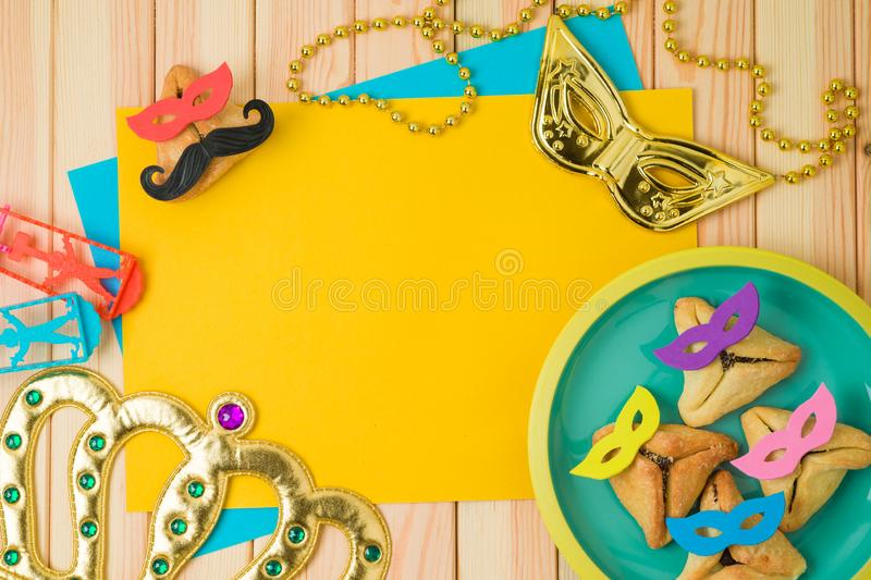 Jewish holiday Purim background with cute funny hamantaschen cookies and paper note on wooden table royalty free stock photo