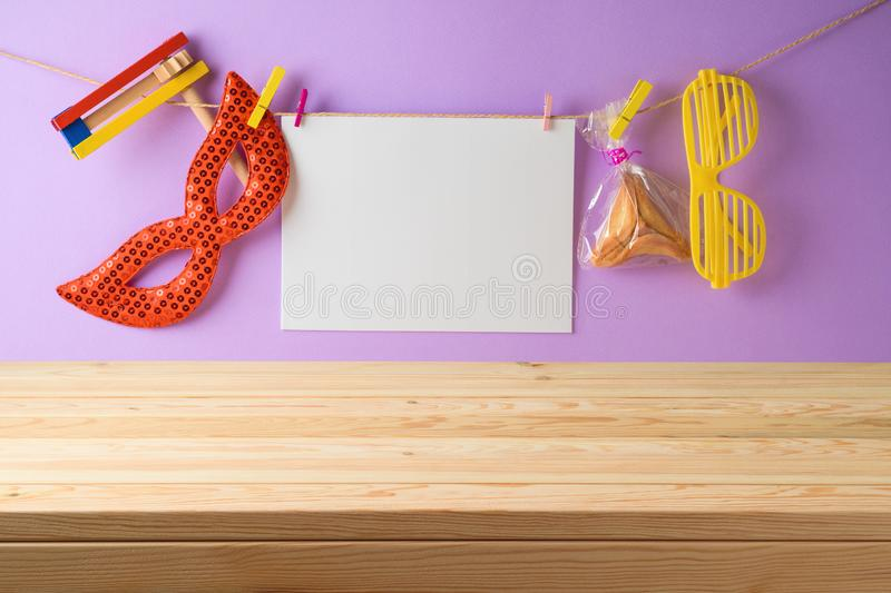 Jewish Holiday Purim holiday background with empty wooden table, paper note, carnival mask and cookie stock photos