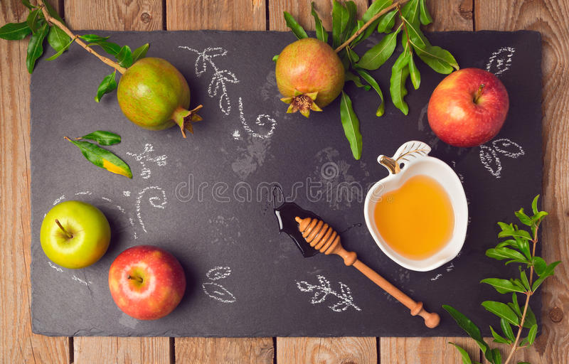 Jewish holiday Rosh Hashana background with apples, pomegranate and honey on blackboard. View from above. royalty free stock image