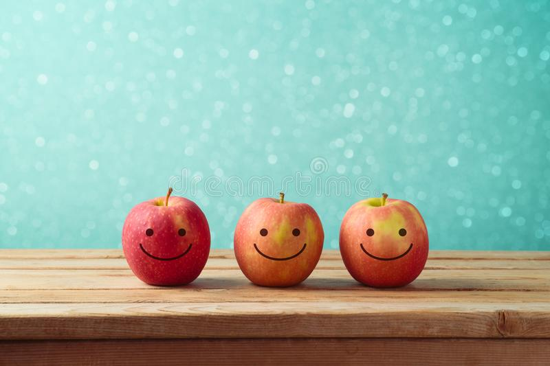 Jewish holiday Rosh Hashanah background with smiling apples. On wooden table royalty free stock photo