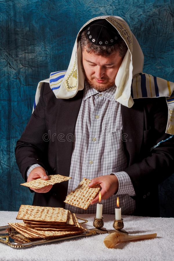 Jewish men is blessings matza for the Jewish holiday of Passover Seder meal. Jewish man is blessing on Matzah unleavened bread while another wearing a kippah royalty free stock photography